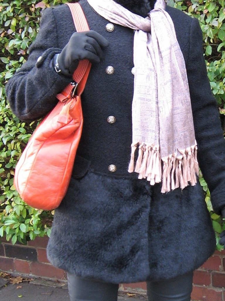 A black, boucle with faux fur, double breasted winter jacket worn with a metallic, rose gold scarf, faux leather trousers, grey boots and an orange bag.