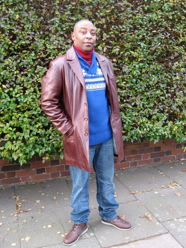 A long, brown leather jacket worn with a beetroot color polo neck, blue V-neck sweater, blue jeans and brown Timberland boots.