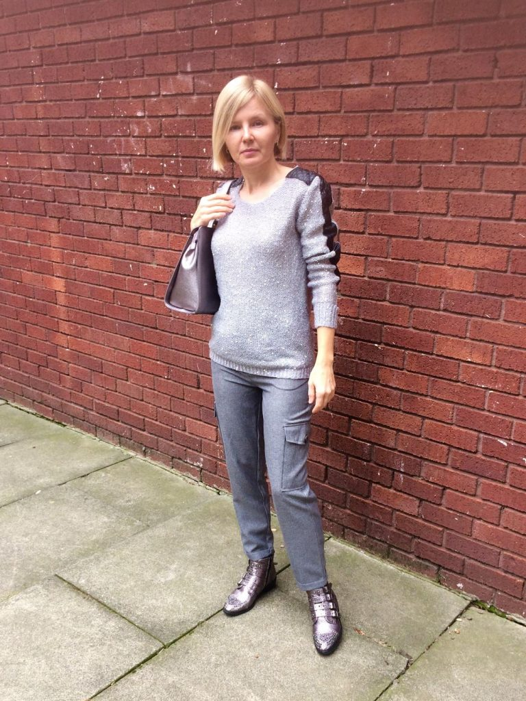 A grey sequined jumper worn with grey cargo pants, Metallic purple shoulder bag and metallic purple, embellished boots.