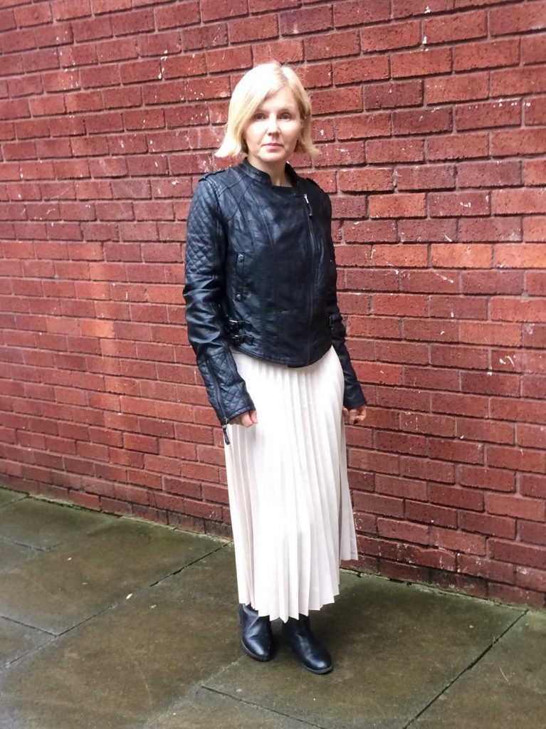 A white, pleated faux leather skirt worn with a short, black faux leather jacket and black over the knee, faux leather boots.