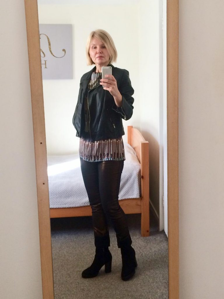 A black, faux leather jacket worn with multi-bronze, brown blouse, metallic, bronze fitted denim and ankle black booties. Styling some old clothes in a different way.