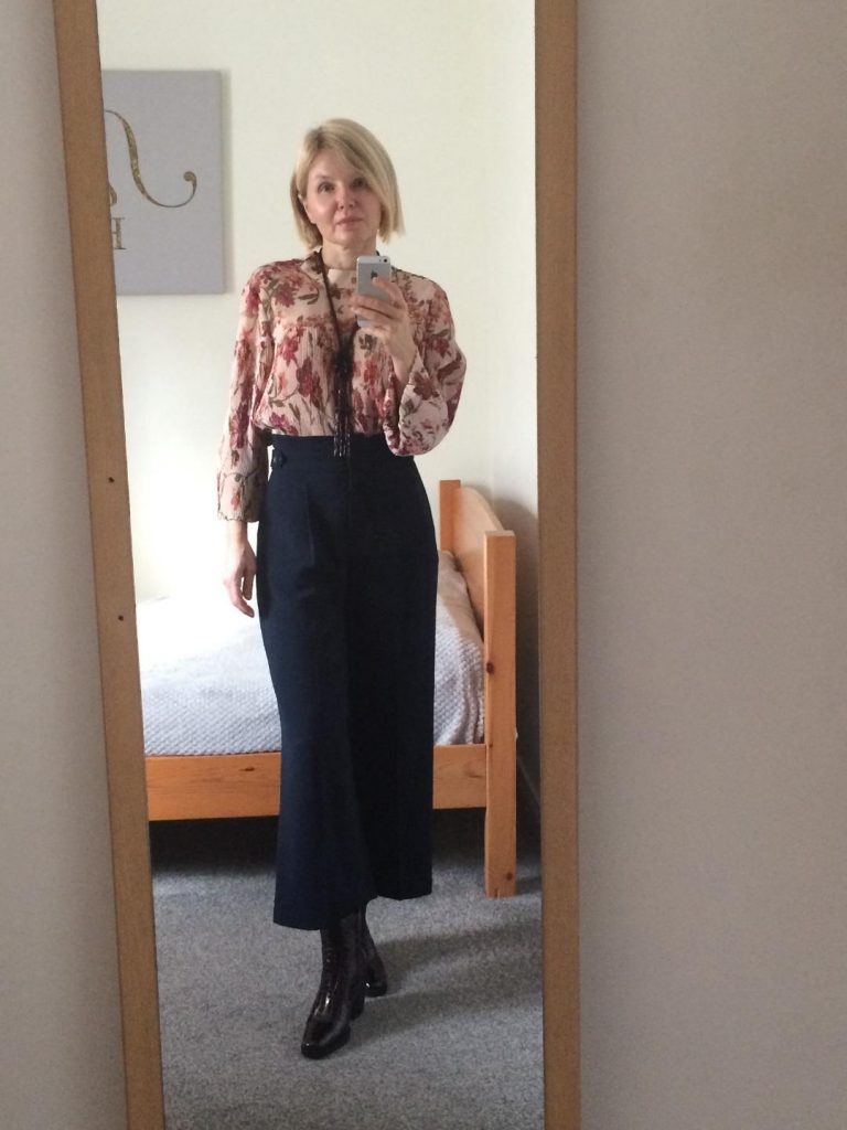 A floral pattern blouse with a golden thread within worn with navy blue culottes, burgundy, patent leather boots and a burgundy necklace.