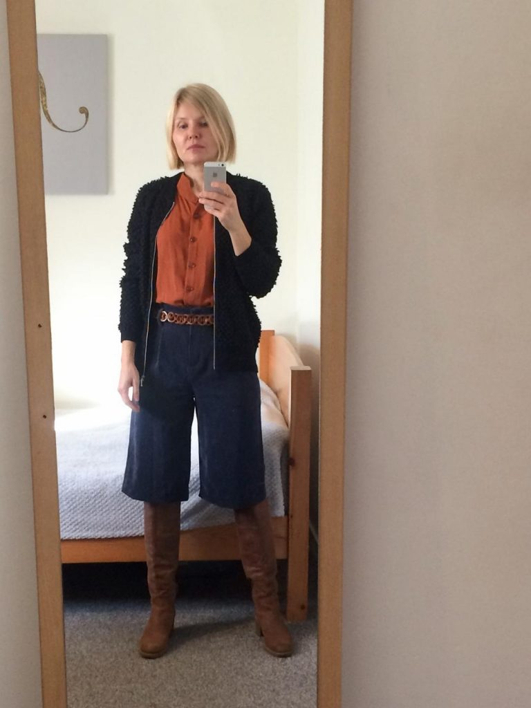 A navy blue bobble cardigan worn with warm brown buttoned-up blouse, navy blue long shorts, brown long boots and a vintage belt.