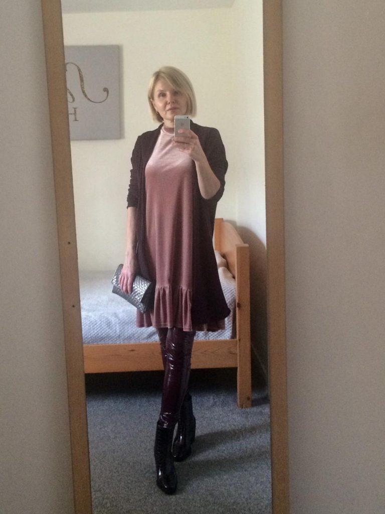 A long, burgundy cardigan worn with dusky pink, velour dress, burgundy, latex leggings, burgundy. boots and a neutral colour clutch bag.