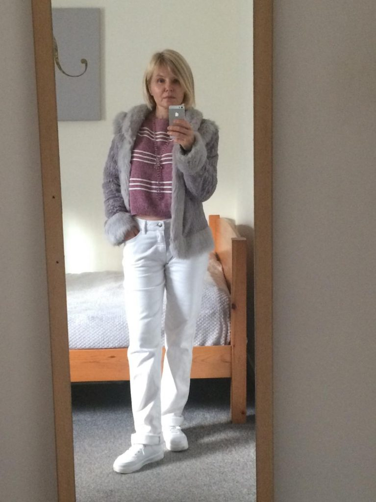 A fluffy, pale grey, short jacket worn with a pink, striped, cropped jumper, beaded, pink necklace, white jeans and white trainers.