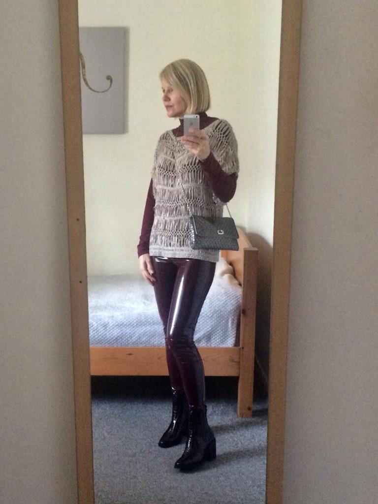 Burgundy latex leggings worn with a burgundy polo-neck, beige-greyish, woven jumper, woven crossbody bag and burgundy boots.