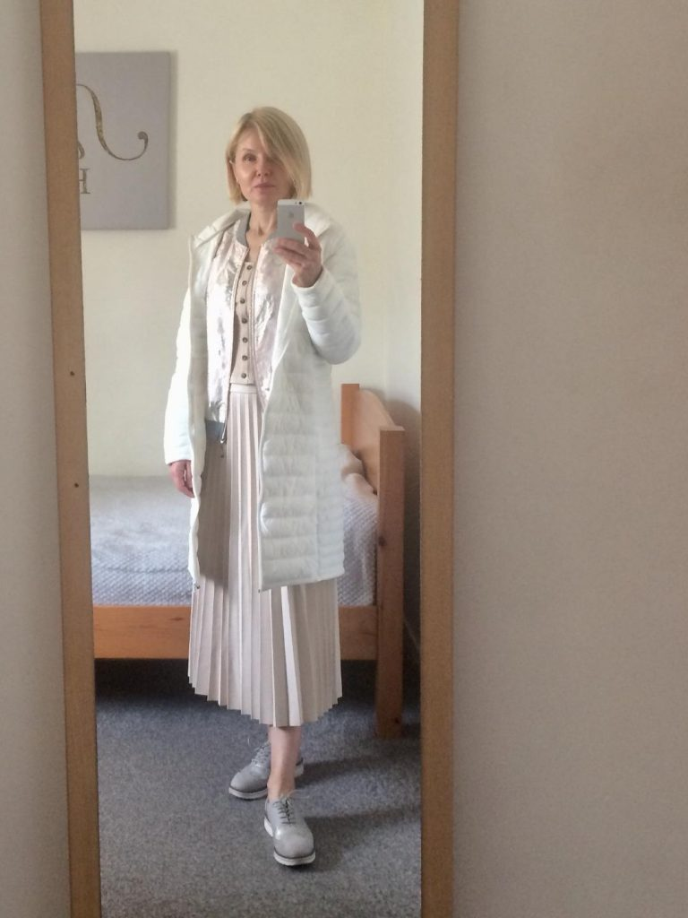A white puffer coat worn with a cream vest, metallic, floral pattern bomber jacket, cream, pleated skirt and pale grey brogues.