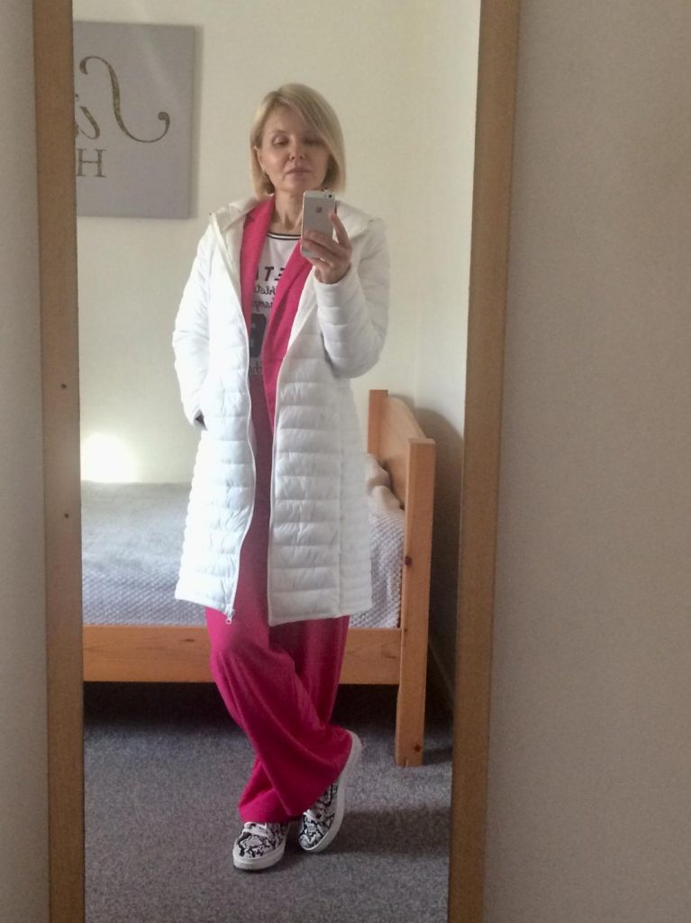 A white, puffer coat worn with an intense pink trouser suit, monochromatic sneak print trainers and monochromatic T-shirt.