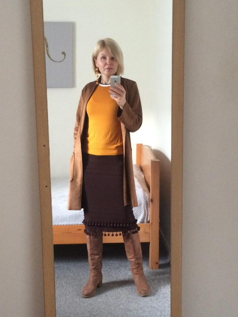 A brown faux suede coat worn with a mustard colour T-shirt, brown dress with pom-poms, brown boots and pom-pom, yellow earrings.