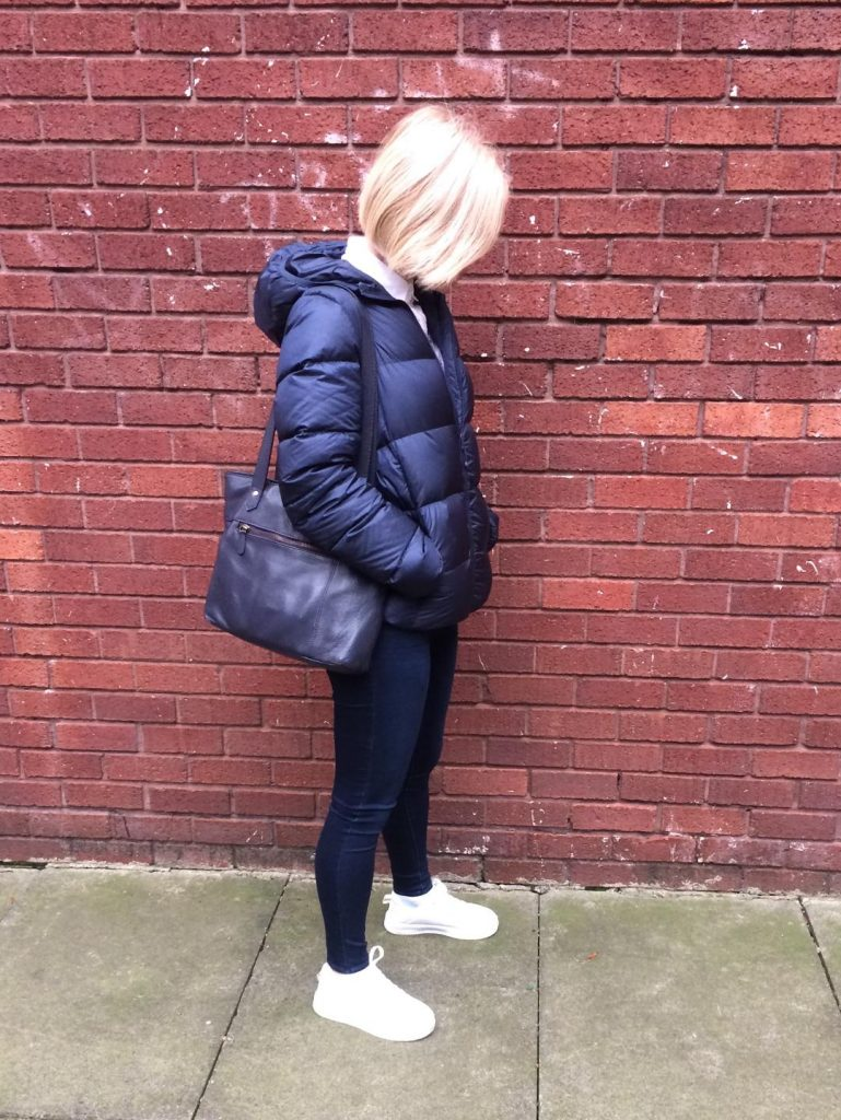 A navy blue puffer jacket worn with navy blue denim, navy blue bag, white broderie anglaise shirt and white trainers.