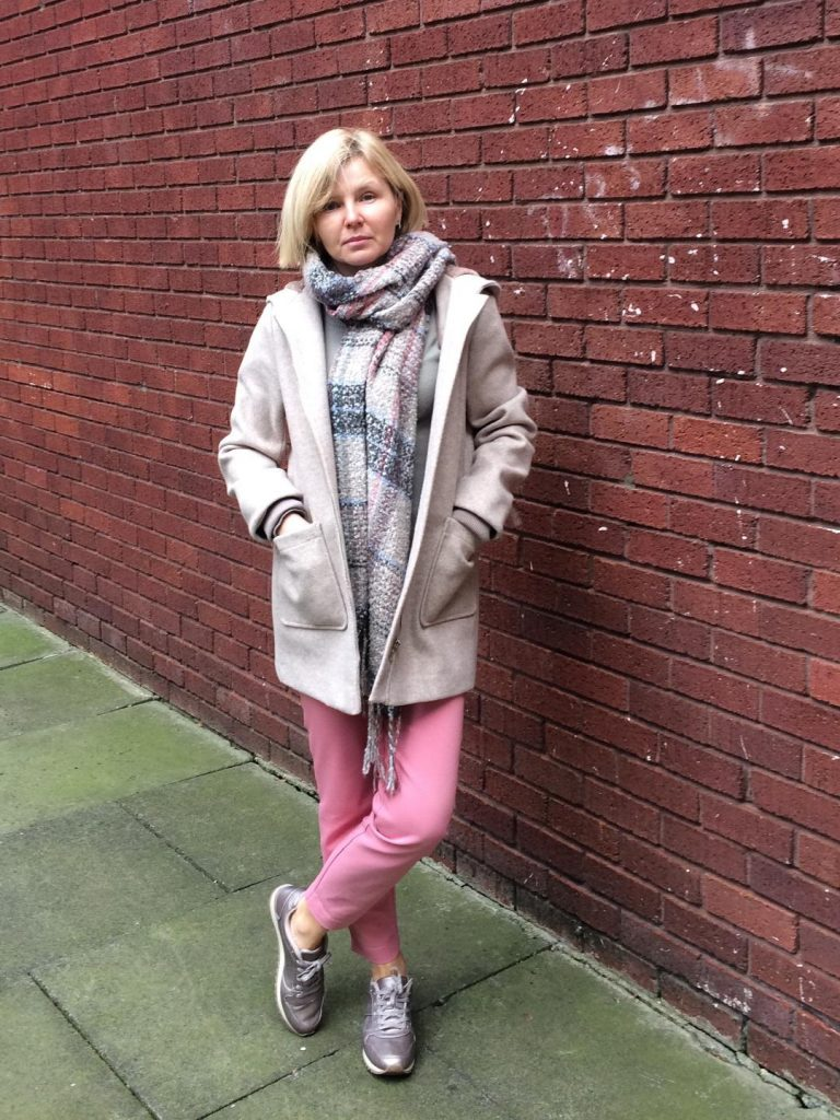 An oatmeal colour winter coat worn with an oatmeal, pink and blue scarf, pink trousers and rose gold trainers.