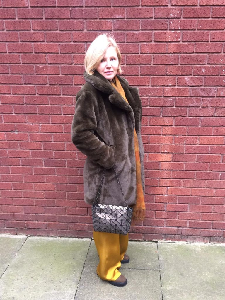 An army green, teddy coat worn with a golden colour scarf, silky, golden, wide-leg trousers and army green bag and boots.