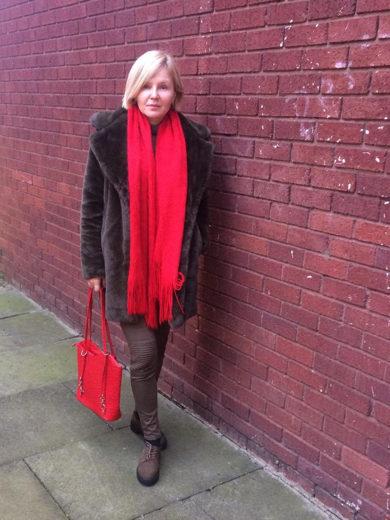 An army green teddy coat worn with army green trousers and boots and a bright red scarf and red shoulder bag.