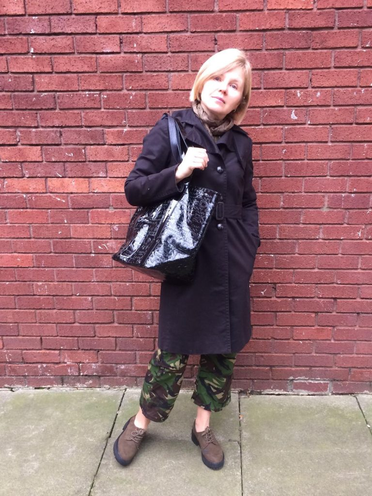 A camo pants worn with a black, classic trench coat, army green scarf, black, reflective shopper and army green boots