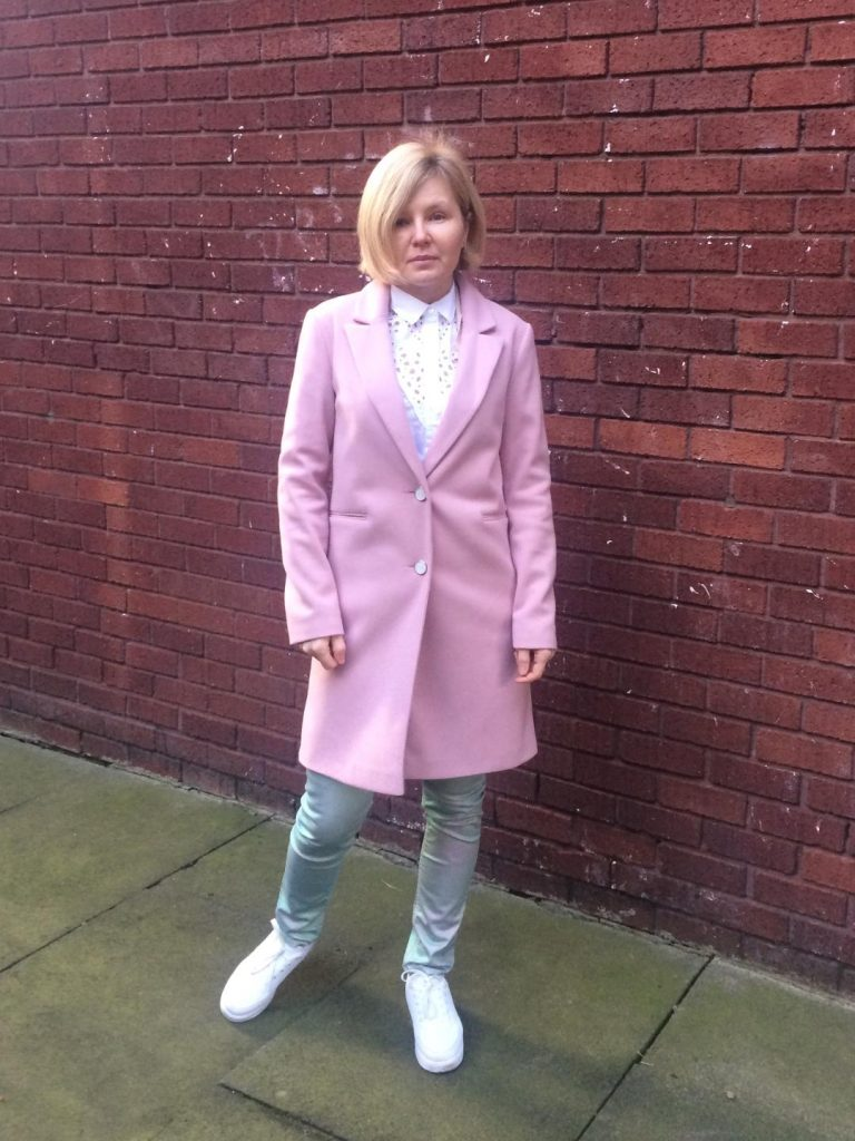 A pale pink single-breasted coat worn with a metallic duo-chrome pink and green trousers, white shirt and white trainers.