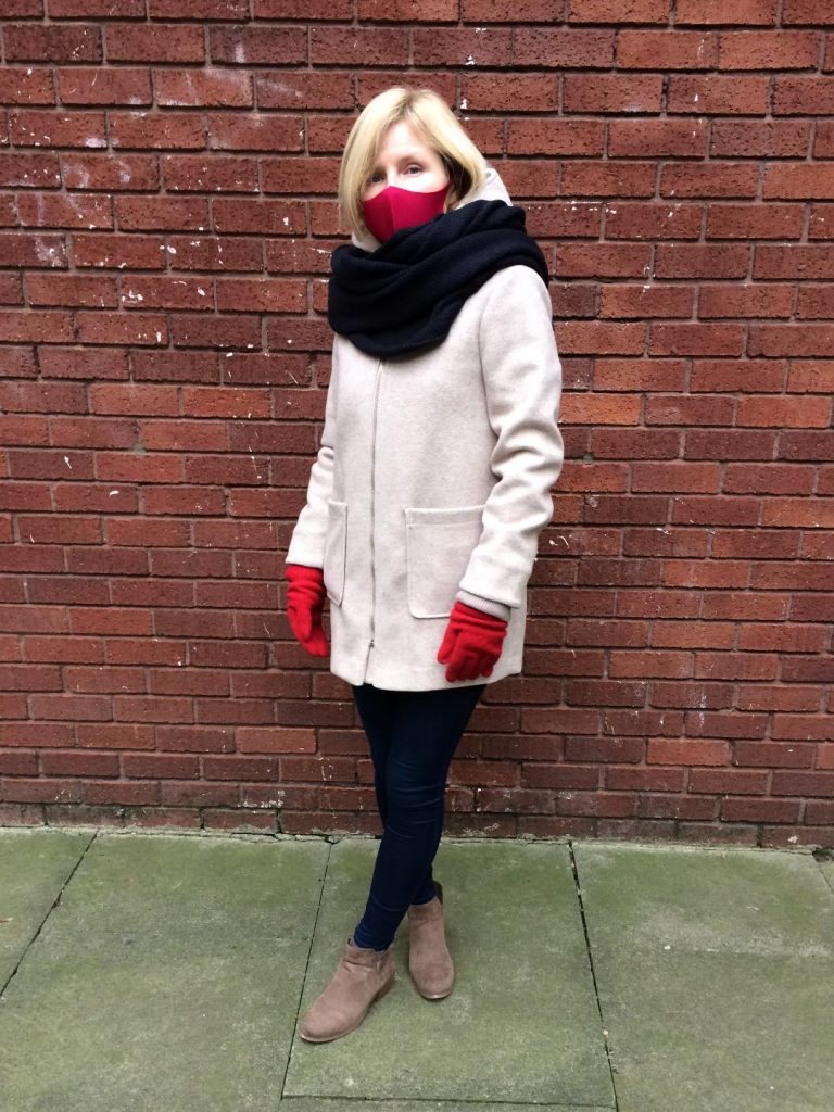 An oatmeal hooded coat worn with a navy blue snoot and jeans, red face mask and gloves and neutral ankle boots.