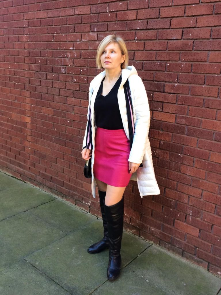 A white, puffer coat worn with black jumper, pink mini skirt, black over the knee boots, black bag and a stripy scarf.