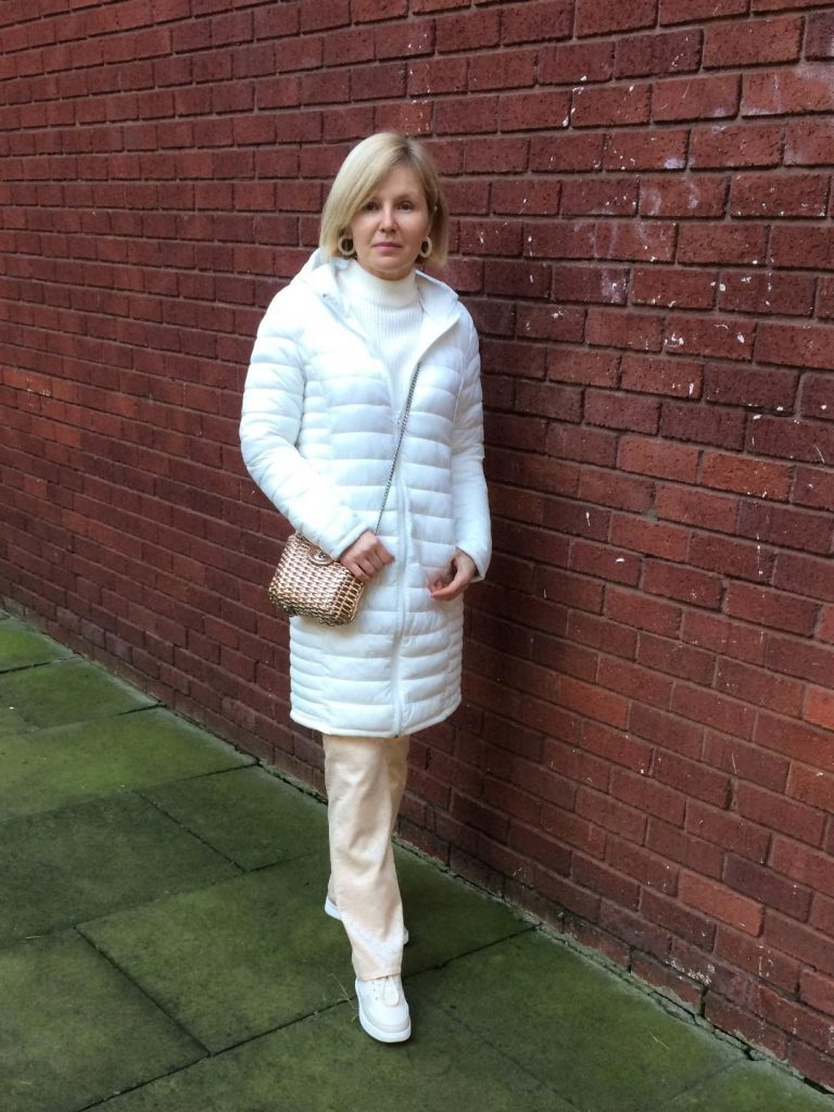 A white puffer coat worn with a white jumper, white earrings, beige trousers, cream trainers and rose-gold bag.