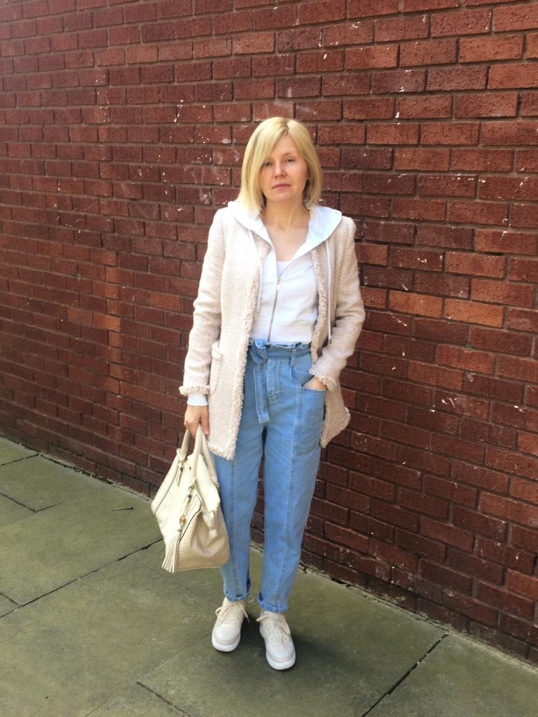 Paper bag waist trousers worn with cropped white hoody, pale pink, long coat, cream bag and cream trainers