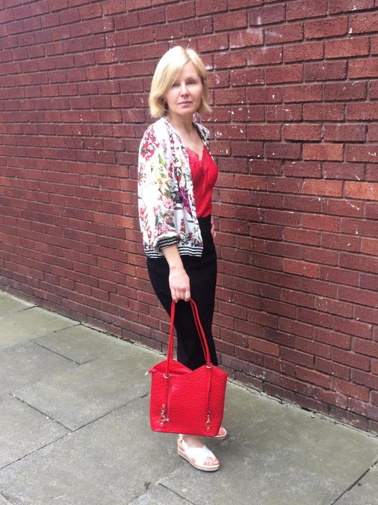 A flowery bomber jacket worn with a lacy red vest, black pencil skirt, red shoulder bag and white summer sandals.