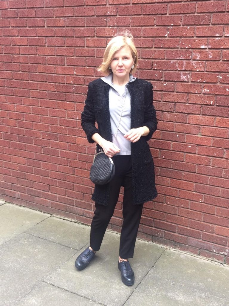 A black coat worn with a grey hoody, black trousers, black quilted cross body bag, black brogues and silver earrrings.