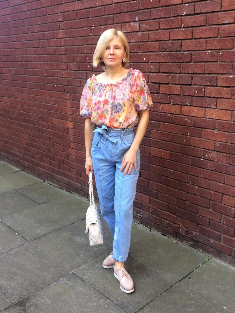 A highly flowery pastel blouse worn with paper bag waist trousers, cream bag and brogues and pearly earrings