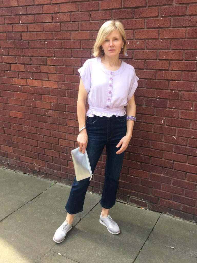 A short, buttoned up pale lavender top with a small peplum worn with cropped denim trousers, and silver grey accesorries.