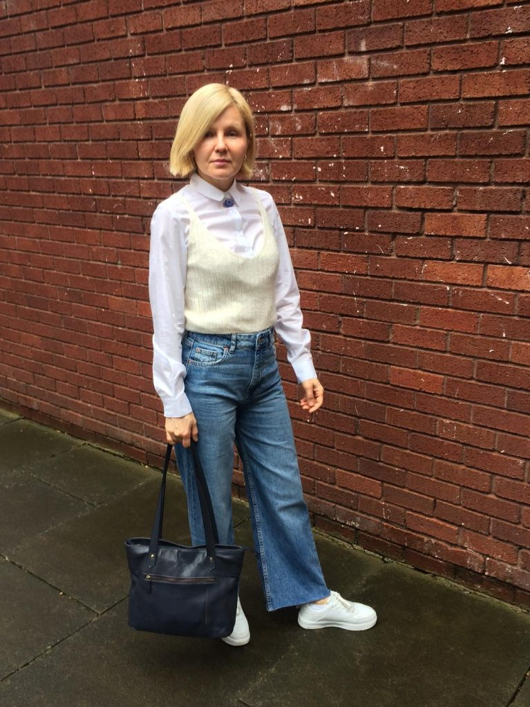 A cropped wide-leg denim trousers worn with a fitted buttoned-up white shirt, cream vest, white trainers and a navy blue bag.