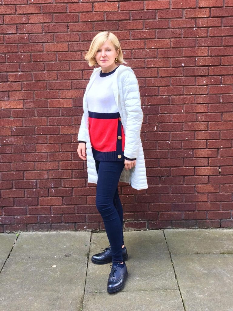 A white, red and navy blue jumper with gold buttons worn with navy blue denim, white coat and navy blue brogues and golden earrings.