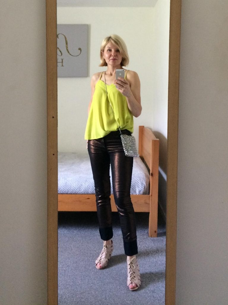 A neon stripy top worn with metallic bronze, fitted trousers, nude laced up wedges and crossbody, sparkling bag